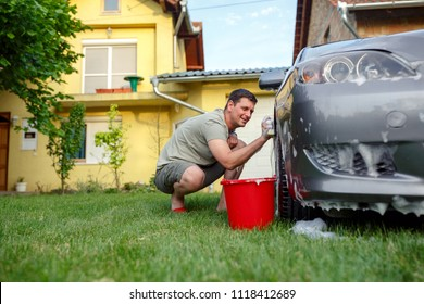 Car washing. Smiling man his cleaning car using sponge and foam in the house yard