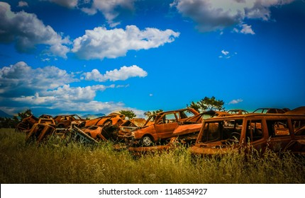 Car waste. Rusty cars on the junkyard. Old rusty abandoned car in the garbage. Corroded cars in car scrapyard. Car recycling