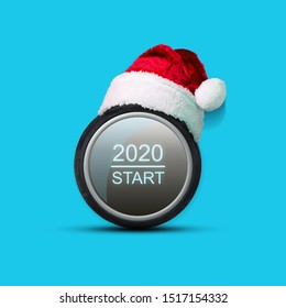 Car wheel, button, start 2020, with a cap of Santa Claus. Isolated on a blue background. Christmas background. Greeting card for a car workshop. Auto mechanics.