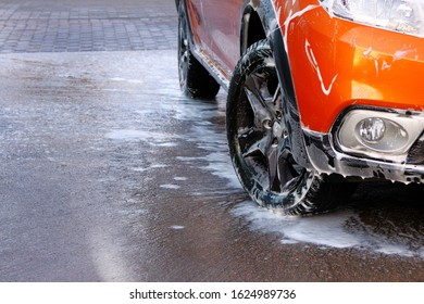 Car wheel close up. Car is cleaning with soap suds at self service car wash. White soapy water runs down.