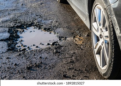 Car wheel close-up near a pothole on the road. Broken asphalt on the  roads. Spring and autumn problems for drivers. Potholes, water pits on a bad road.