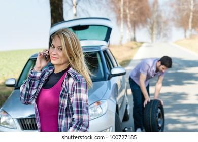 Car wheel defect man change puncture tire woman calling assistance