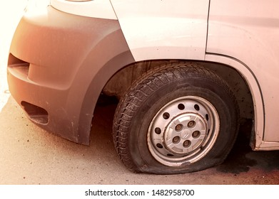 Car wheel flat tire on the road. Small white truck with punctured wheel