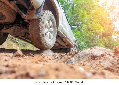 Car wheel on a dirt road. Off-road tire covered with mud, dirt terrain. Outdoor, adventures and travel. Car tire close-up in a countryside landscape. Four wheel truck in mud.