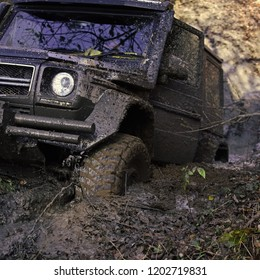 Car wheel on dirt road. Off road tire covered with mud, dirt terrain. Outdoor, adventures and travel SUV with muddy road. All wheel drive car in puddle of mud.