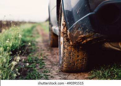 Car wheel on a dirt road. Off-road tire covered with mud, dirt terrain. Outdoor, adventures and travel suv. Car tire close-up in a countryside landscape with a muddy road. Four wheel truck in mud.