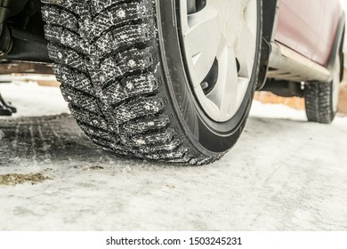 Car wheel on a slippery snowy winter road. Winter studded tires.