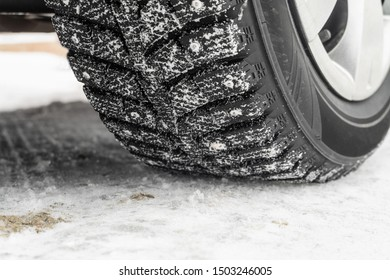 Car wheel on a slippery snowy winter road. Deep tread of winter studded tires close-up.