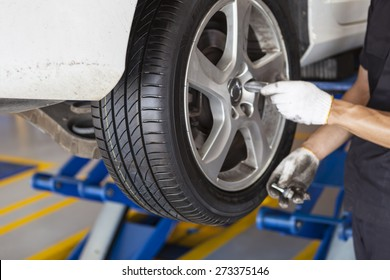 car wheel tire replacement on the scissor cranes by hands of mechanic in the garage