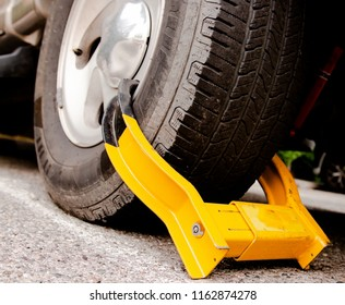 car wheel tire with yellow boot in parking lot close up dramatic angle