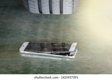 car wheel is trampled on a mobile phone that makes it to broken