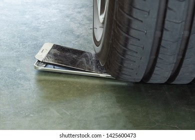 car wheel is trampling on a mobile phone that makes it to broken