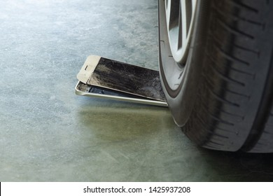 car wheel is trampling on a mobile phone that made it to broken