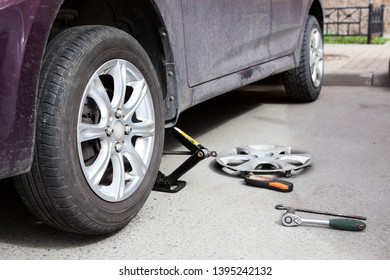 Car whell change, adjustable jack under front side of vehicle, tools are on asphalt