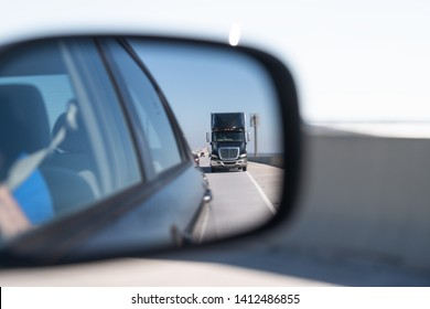 Car window side mirror on sunny day with truck traffic in reflection in Florida transporation highway street road