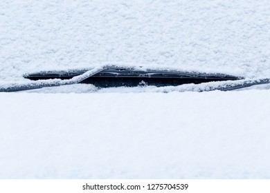 Car window wiper covered full of snow. Front close up full frame shot with text space below