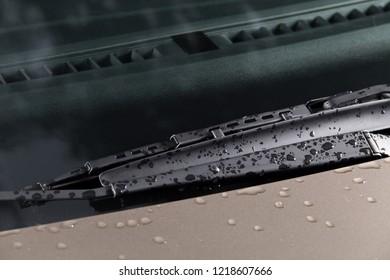 Car windshield wiper with raindrops close-up. New car wiper.