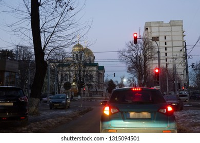 Car in a winter city stands at a traffic light