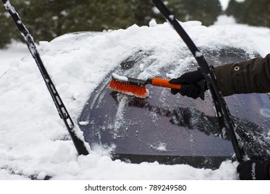 car, winter, people and vehicle concept - close-up of a man, cleans a car from snow