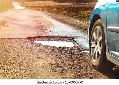 Car and winter pothole on open road