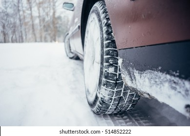 Car with winter tire on snowy road, defocused image