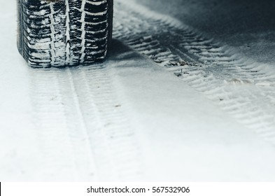Car with winter tyres installed in snowy road outdoors