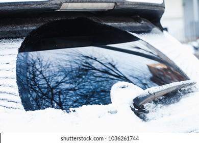 Car wiper on rear window with snow in cold winter season