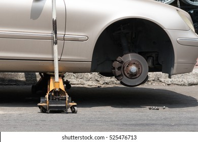Car without wheel and lift up by hydraulic, waiting for tire replacement.