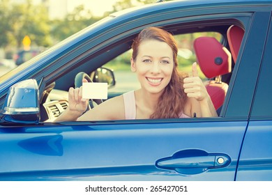 Car. Woman driver happy smiling showing thumbs up coming out of car window on summer day