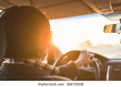 A car woman driver is travelling while the light of the sunset hits her face.