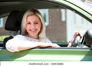 Car woman happy in small green car. Attractive young woman driving on road trip on sunny summer day