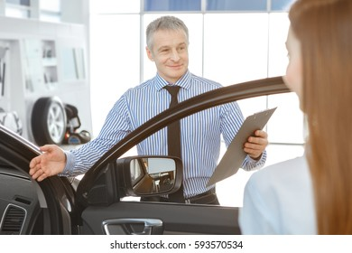 Car for a woman. Mature male car dealer inviting his female customer to sit in a new car. woman buying car at the dealership communication manager offer sale business profession occupation safety