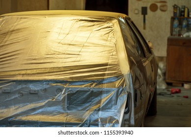 The car wrapped in a paper prepared for painting in body shop.