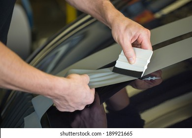 Car wrapper straightening wrapping foil with a squeegee to remove air bubbles