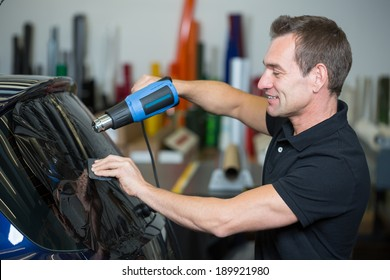 Car wrapper tinting a vehicle window with foil