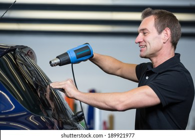 Car wrapping specialist attaching tinting foil to car window