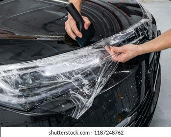 Car wrapping specialist putting vinyl foil or film on car. Protective film. Applying a protective film with tools for work. Car detailing. Transparent film. Car paint protection. Trimming
