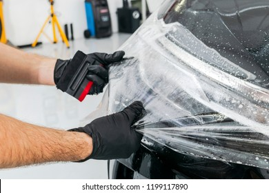 Car wrapping specialist putting vinyl foil or film on car. Protective film. Applying a protective film with tools for work. Car detailing. Transparent film. Car paint protection.