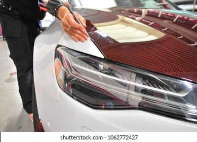 Car wrapping specialists straightening vinyl foil or film to remove ari bubbles cut carbon film