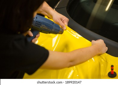 Car wrapping specialists using heat gun to prepare vinyl foil