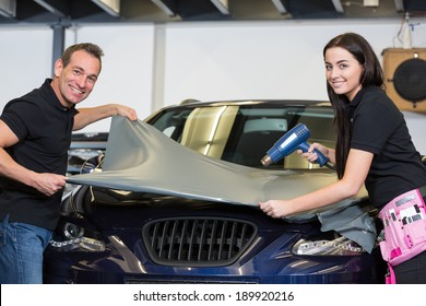 Car wrapping specialists wrapping a vehicle with grey vinyl film or foil