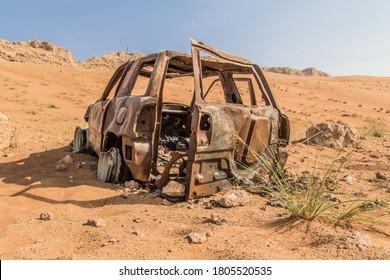Car wreck in the desert near Dubai. Burned and rosty.