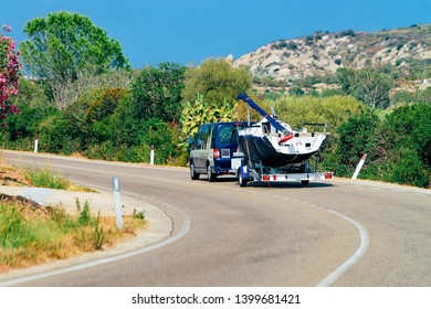 Car with yacht or motor boat in the road of Costa Smeralda in Sardinia in Italy in summer. Auto with motorboat on the highway in Europe. View on moped on motorway.