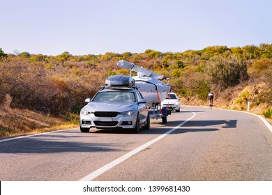 Car with yacht or motor boat at the road of Costa Smeralda in Sardinia island in Italy in summer. Auto with motorboat on the highway in Europe. View on moped on motorway.