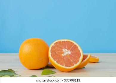 Cara orange on wooden table over blue background.