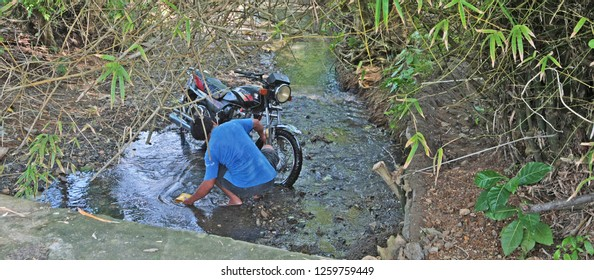 Carabao, Philippines - August 11, 2011: A man washing his motorbike in a creek in Carabao, Philippines. Motorcycles are a popular and economical form of transportation throughout Asia.