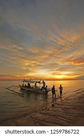 Carabao, Philippines - August 12, 2011: Men disembarking from a small boat on Carabao Island, Philippines. Suitable to illustrate tropical destinations, exotic islands, sunsets, boating, and fishing.