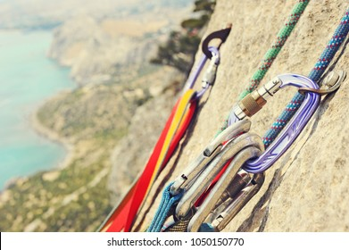 Carabiner with climbing rope on rocky background. Climbing concept. Climbing extreme sport