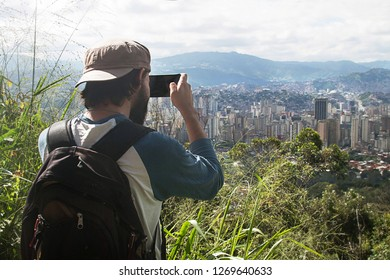 Caracas, Capital District / Venezuela - 11 22 2018: Man taking a photo of cityscape in the city of Caracas, Caracas, Capital District, Venezuela, South America