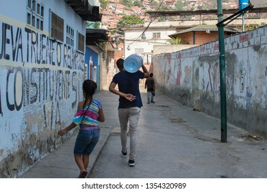 Caracas, Venezuela; 03 30 2019; A young man carries a 5-gallon bottle of water on his shoulders in El Valle slum, Caracas. Venezuelans now suffer a lack of water due to latest power blackouts